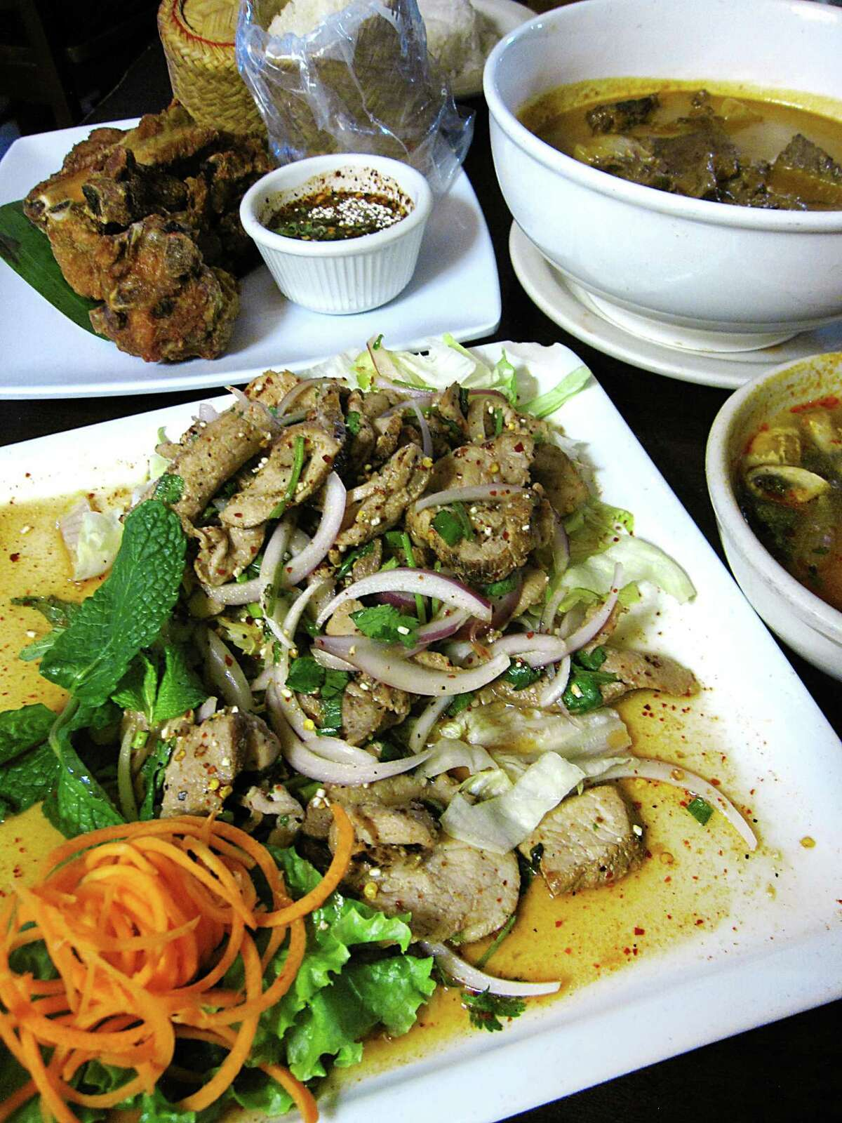 Clockwise from front: Nam tok with pork, fried pork ribs, massaman curry with beef and tom yum soup
