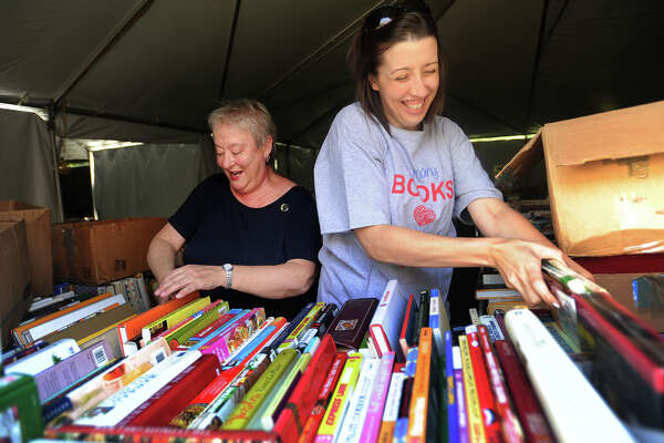 Adair Heitmann, left, of Fairfield, and Victoria Konopka, of Oxford, put out books for the 57th Annual Summer Book Sale at the Pequot Library in Southport, Conn. on Wednesday, July 19, 2017. The book sale runs from Friday, July 21 to Tuesday, July 25 with hours from 9 a.m. to 6 p.m. from Friday through Monday and 9 a.m. to 2 p.m. on Tuesday. Proceeds from the sale support the library and its programs. This year's sale features over 140 thousand books.