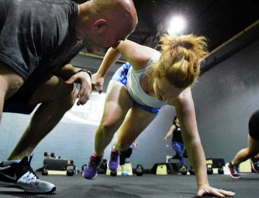 Head trainer James Wilson, left, coaches Times Union writer Leigh Hornbeck as she tries a class at Metabolic Meltdown Wednesday June 21, 2017 in Colonie, NY. (John Carl D'Annibale / Times Union)