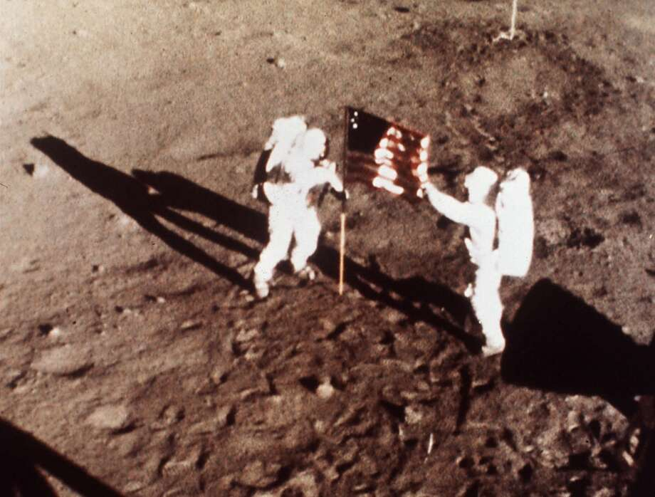 "Apollo 11 astronauts Neil Armstrong and Edwin E. ""Buzz"" Aldrin, the first men to land on the moon, plant the U.S. flag on the lunar surface, July 20, 1969. Photo was made by a 16mm movie camera inside the lunar module, shooting at one frame per second.  Photo: HO / NASA"