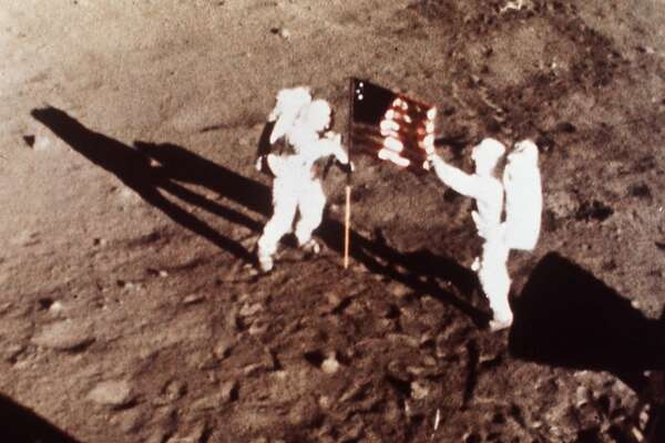 "Apollo 11 astronauts Neil Armstrong and Edwin E. ""Buzz"" Aldrin, the first men to land on the moon, plant the U.S. flag on the lunar surface, July 20, 1969. Photo was made by a 16mm movie camera inside the lunar module, shooting at one frame per second. The moonwalk is among the top stories of the century selected by a group of prominent journalists and scholars polled by the Newseum in Arlington, Va. (AP Photo/NASA)"