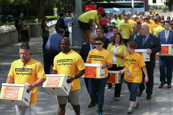 Houston firefighters deliver boxes of more than 32,000 signatures to City Hall on Monday asking voters in November to mandate parity in pay between firefighter and police officer ranks.