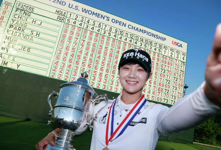 """Sung Hyun Park of Sourth Korea imitates a """"selfie"""" with the championship trophy after winning the U.S. Women's Open Championship at Trump National Golf Club on Sunday in Bedminster, N.J.  (Photo by Matt Sullivan/Getty Images)"""