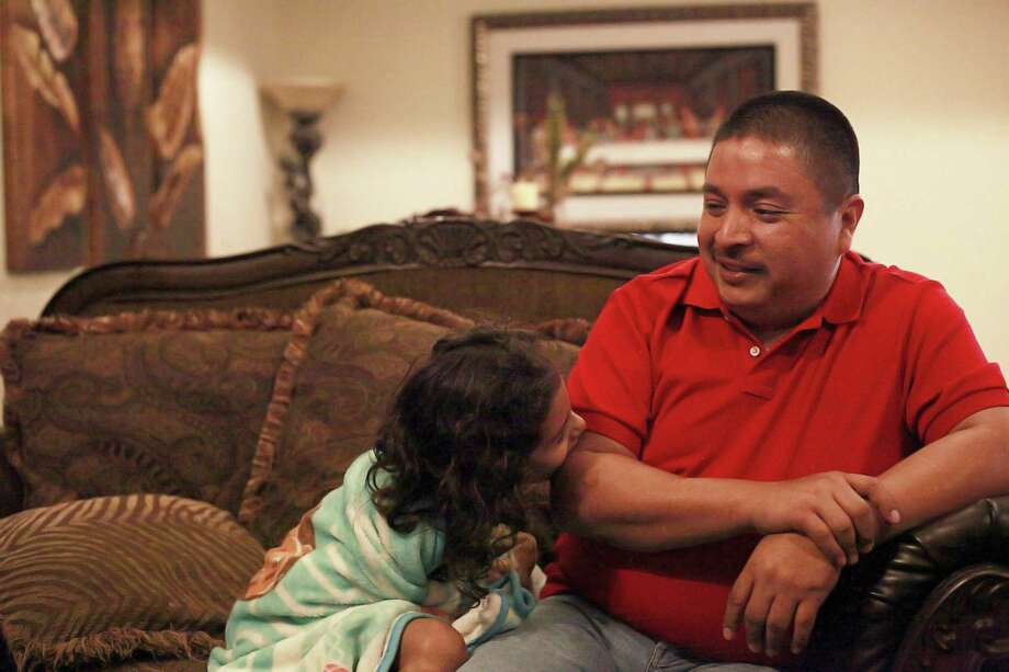 In a recent Supreme Court ruling, Leonardo Villegas, 42, was left without a home to call his own. Born a Mexican and raised in the Eagle Pass area of Texas, Villegas has tired to claim citizenship to stay in U.S.A. through his U.S. born father, but, was denied citizenship because his parents were not married. Villegas, sits on his couch with his youngest daughter, Keyla, 6, as they watch cartoons on television. Photo: Srijita Chattopadhyay, Staff / San Antonio Express-News / © 2017 San Antonio Express-News