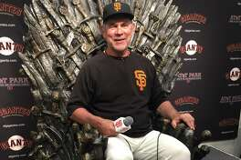 """Giants manager Bruce Bochy sits in the iron thrown from the """"Game of Thrones"""" television program, which was brought to AT& Park on Wednesday ahead of Game of Thrones night on Thursday"""