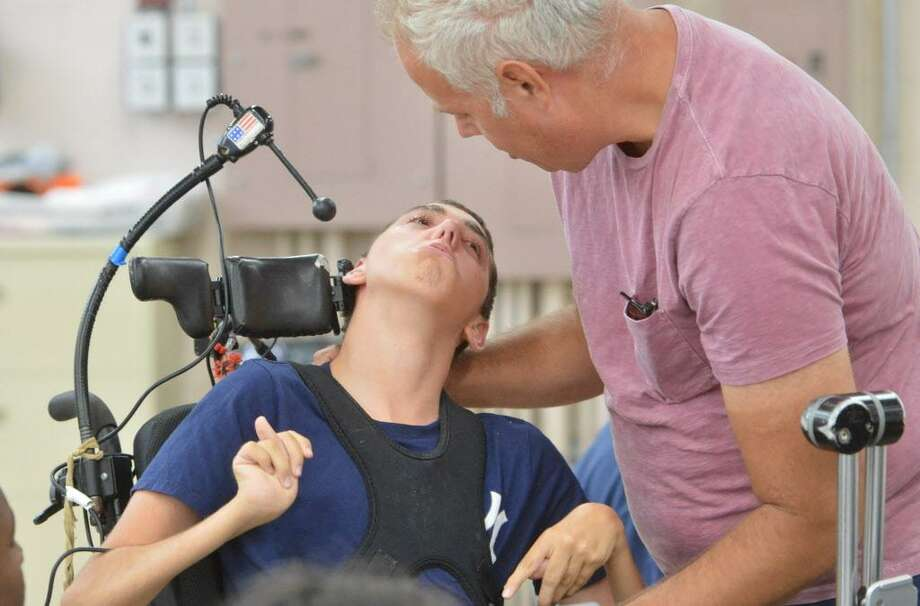 Brett Davis stops by to see his son Wyatt who suffers with cerebral palsy while he sits with others during a craft program at Star's facility on Monday July 17, 2017 in Norwalk Conn. Star and its client families will be directly impacted by the six furlough days ordered by the state when no services will be available  on those days. Photo: Alex Von Kleydorff / Hearst Connecticut Media / Norwalk Hour