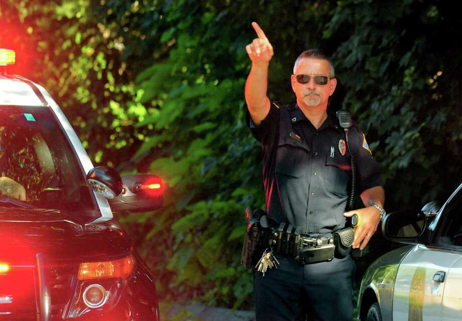 A Shelton police officer directs traffic at Sunnyside Middle School as the department investigate the death of a 46-year-old man pronounced dead after drowning in the Housatonic River at the Sunnyside Boat Ramp in Shelton, Conn., on Wednesday July 19, 2017. Police responded to the boat launch off River Road in Shelton around 2 p.m., Lt. Robert Kozlowsky said. He said police received calls for a male in the water in distress that had gone under. Photo: Christian Abraham / Hearst Connecticut Media / Connecticut Post