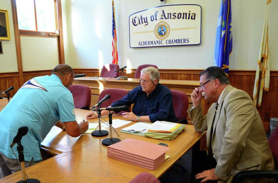 Joseph Gega, with USA Management, at left, puts in a $110,000 bid in for the former Anaconda American Brass site during an auction held at Ansonia City Hall in Ansonia, Conn., on Wednesday July 19, 2017. Officiating the auction is Connecticut State Marshal Arthur Davies, center, and Attorney Kevin Condon. Photo: Christian Abraham / Hearst Connecticut Media / Connecticut Post