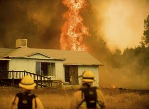 Flames rise behind a vacant house as firefighters work to halt the Detwiler fire near Mariposa, Calif., Wednesday, July 19, 2017.
