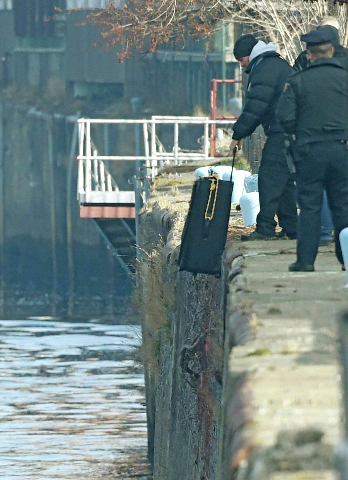 A member of the law enforcement drops a suitcase in to the water to determine what tides will do as the search of the Hudson River continues for Noel Alkaramla early Tuesday morning Dec. 8, 2015 in the area of Troy, N.Y. Alkaramla has been missing since Nov. 22nd. (Skip Dickstein/Times Union)