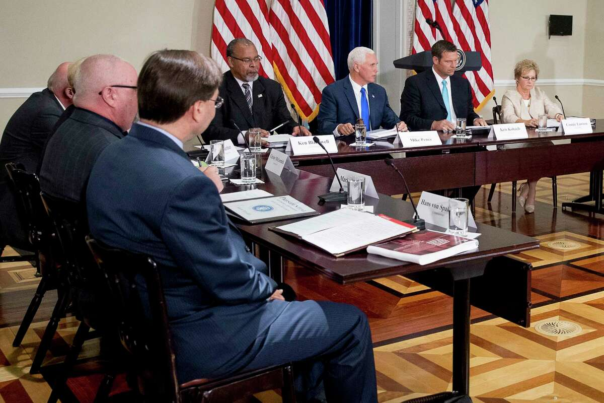 Vice President Mike Pence, third from right, accompanied by former Mayor of Cincinnati Ken Blackwell, fourth from right, Kansas Secretary of State Kris Kobach, second from right, and Indiana Secretary of State Connie Lawson, right, gavels in for the first meeting of the Presidential Advisory Commission on Election Integrity at the Eisenhower Executive Office Building on the White House complex in Washington, Wednesday, July 19, 2017. (AP Photo/Andrew Harnik)