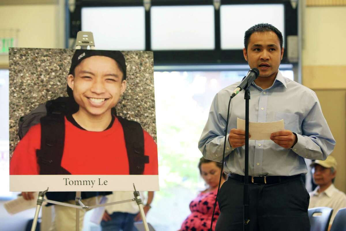 Tommy Le's older brother, Quoc Nguyen, speaks next to a photo of Le.