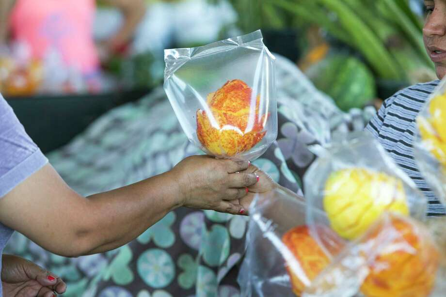 Shoppers buy fruit at the farmer's market in the 2500 block of Arline on Monday, May 1, 2017, in Houston. A local developer is under contract to purchase the farmer's market property in the Heights area. The group says the market will stay, but improvements are planned that will affect the property in the long term.  ( Brett Coomer / Houston Chronicle ) Photo: Brett Coomer, Staff / Stratford Booster Club