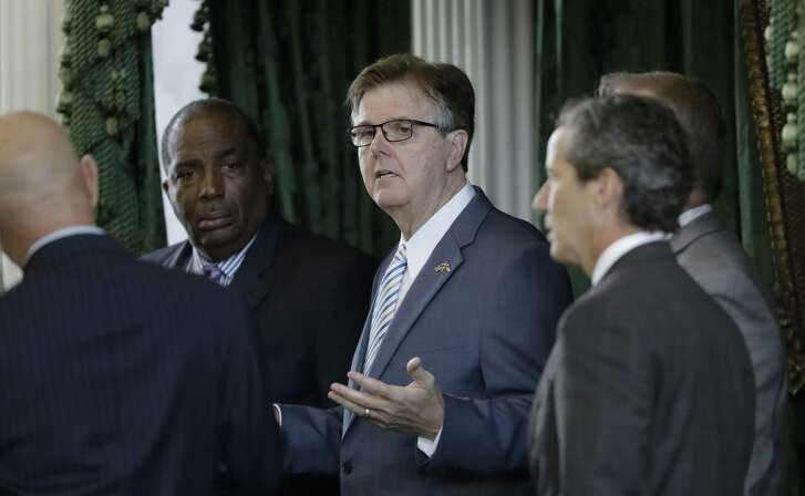 Lt. Gov. Dan Patrick, center, talks with state senators on the second day of a special session ordered by Republican Gov. Greg Abbott, in Austin, Texas, Wednesday, July 19, 2017. Conservatives in the state Senate are swiftly advancing sunset legislation, a regulatory bill that must pass before the legislature can work on anti-abortion measures, school vouchers and defanging local ordinances in Texas' big and liberal cities. (AP Photo/Eric Gay)