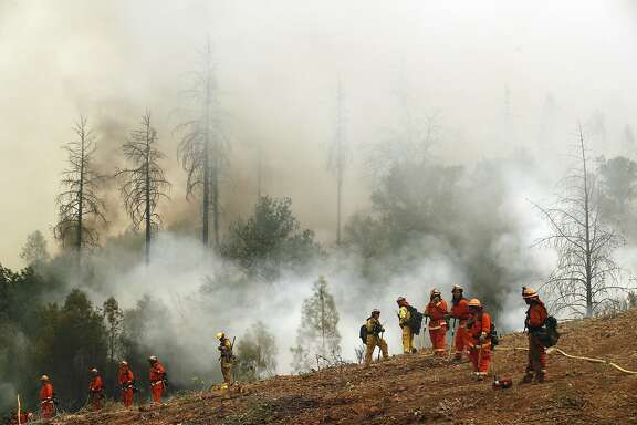An inmate firefighter team out of the McCain Valley keeps watch on a fire line as they continue to battle the Detwiler Fire on the outskirts of Mariposa, Ca., on Wednesday July 19, 2017.