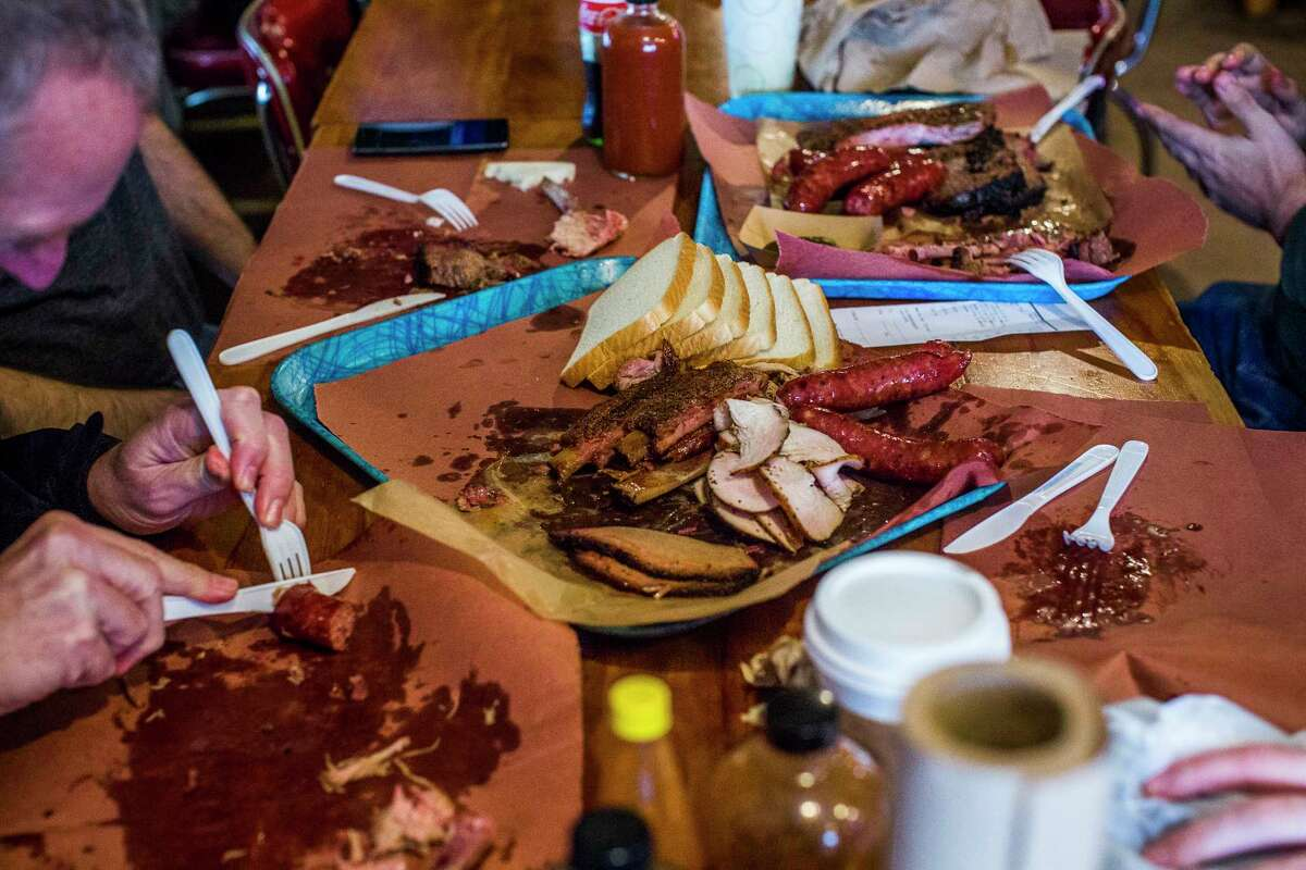 Barbecue fans digging into Franklin Barbecue smoked meats. The barbecue joint, damaged in a fire in August, reopened Nov. 21.