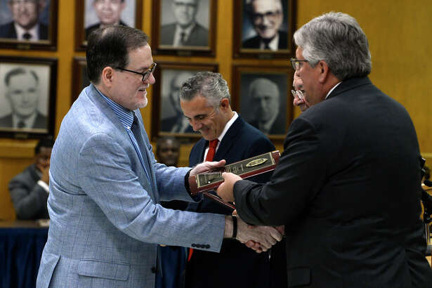 Superintendent John Frossard hands a plaque to manager Jack Carroll during the Beaumont ISD board meeting on Wednesday. The meeting was the last meeting for managers Lenny Caballero, Jimmy Simmons and Carroll, who have resigned.  Photo taken Wednesday 7/19/17 Ryan Pelham/The Enterprise