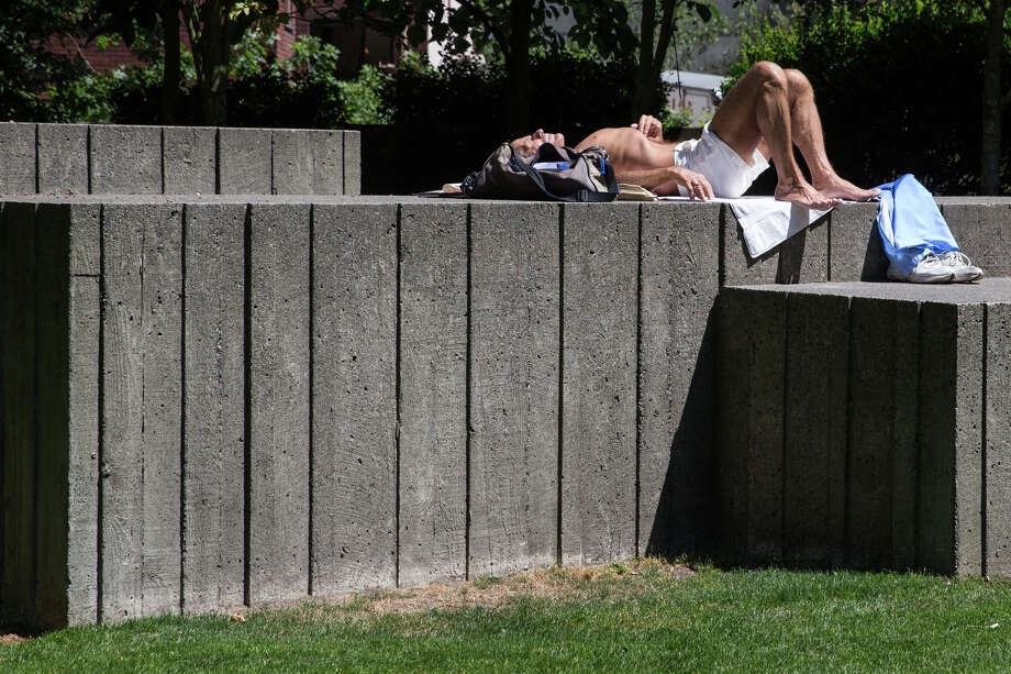 A man enjoys the sunshine from atop one of Freeway Park's signature Brutalist landing pads, on Wednesday, July 19, 2017. Photo: GRANT HINDSLEY, SEATTLEPI.COM / SEATTLEPI.COM