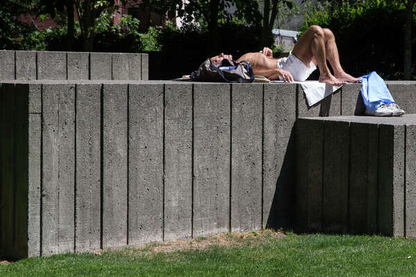 A man enjoys the sunshine from atop one of Freeway Park's signature Brutalist landing pads, on Wednesday, July 19, 2017.