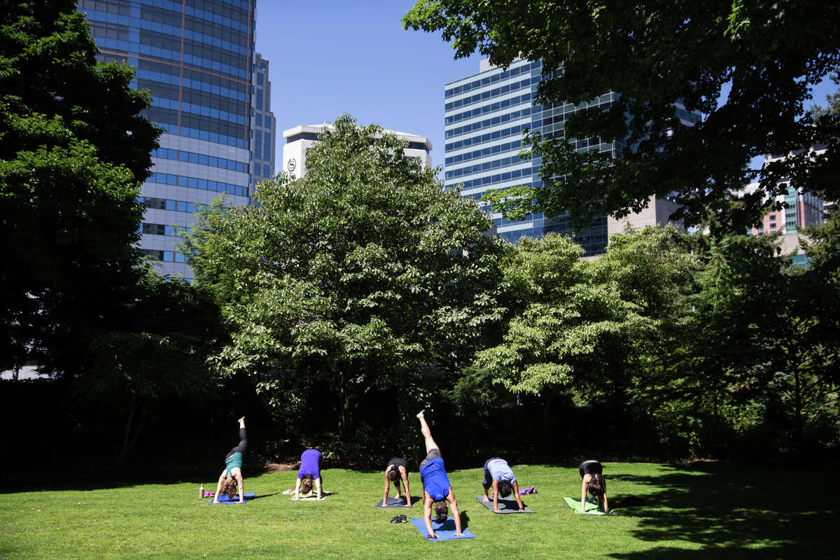 Yoga in front of the city at Freeway Park, seen on Wednesday, July 19, 2017.