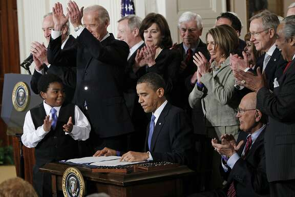 FILE -In this March 23, 2010, file photo President Barack Obama is applauded after signing the Affordable Care Act into law in the East Room of the White House in Washington. If the law survives Supreme Court scrutiny, it will be nearly a decade before all its major pieces are in place, and even if he is re-elected, Obama won't be in office to oversee completion of his biggest domestic policy accomplishment, assuming Republicans don't succeed in repealing it. The law's carefully orchestrated phase-in is evidence of what's at stake in the Supreme Court deliberations that start March 26, 2012. (AP Photo/Charles Dharapak, File)