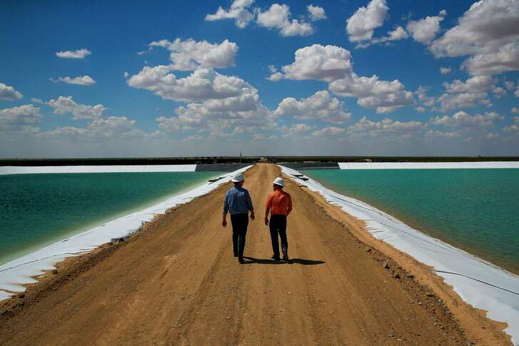 Layne Christensen's Byron Bevers, left, and Tim Patrick walk between water retention ponds for the new project in Pecos.