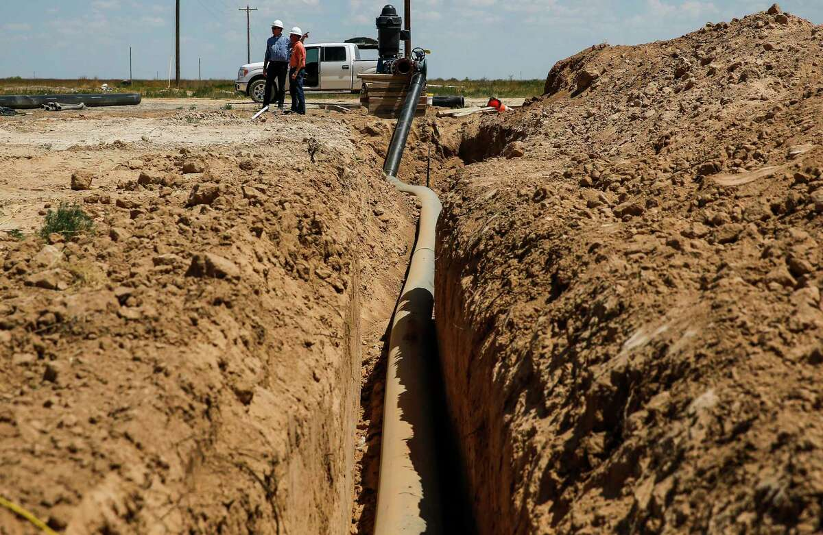 Layne Christensen principal business development engineer Byron Bevers, left, and business developer Tim Patrick stand next to a lay flat hose that connects a water well to their new pipeline Tuesday, July 18, 2017 in Pecos. The Woodlands based company is building a facility to supply water for hydraulic fracturing operations in the Delaware Basin. ( Michael Ciaglo / Houston Chronicle )