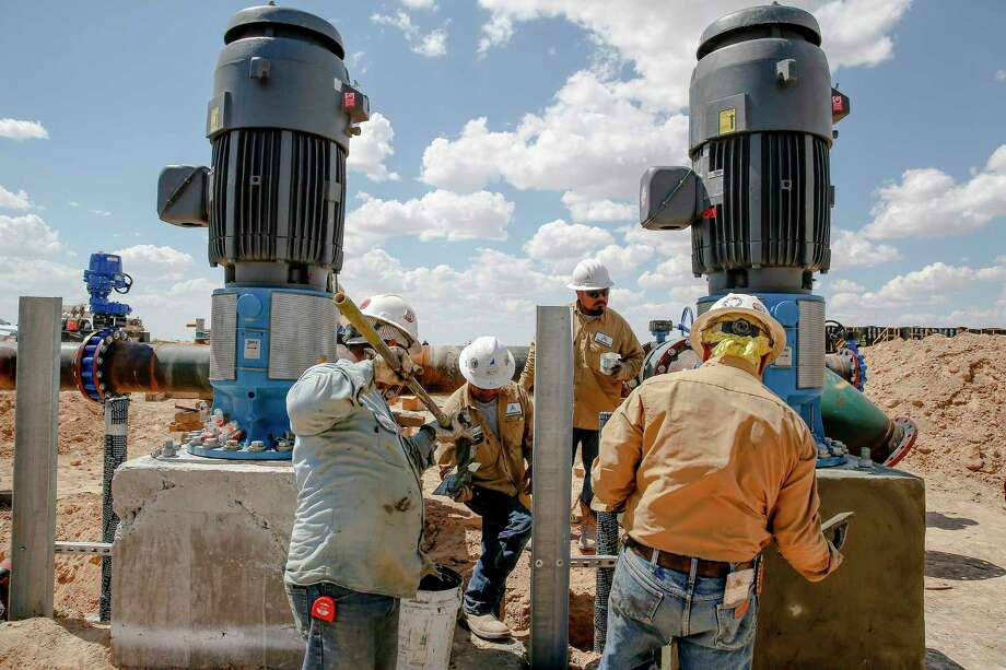 Contractors work on two water pumps that will push water through a 20-mile pipeline at Layne Christensen's new property in Pecos to supply water for hydraulic fracturing operations in the Delaware Basin. Photo: Michael Ciaglo, Staff / Michael Ciaglo