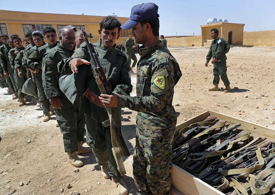 Syrian Internal Security Forces receive weapons during their graduation ceremony in Raqqa province. Photo: Hussein Malla, Associated Press