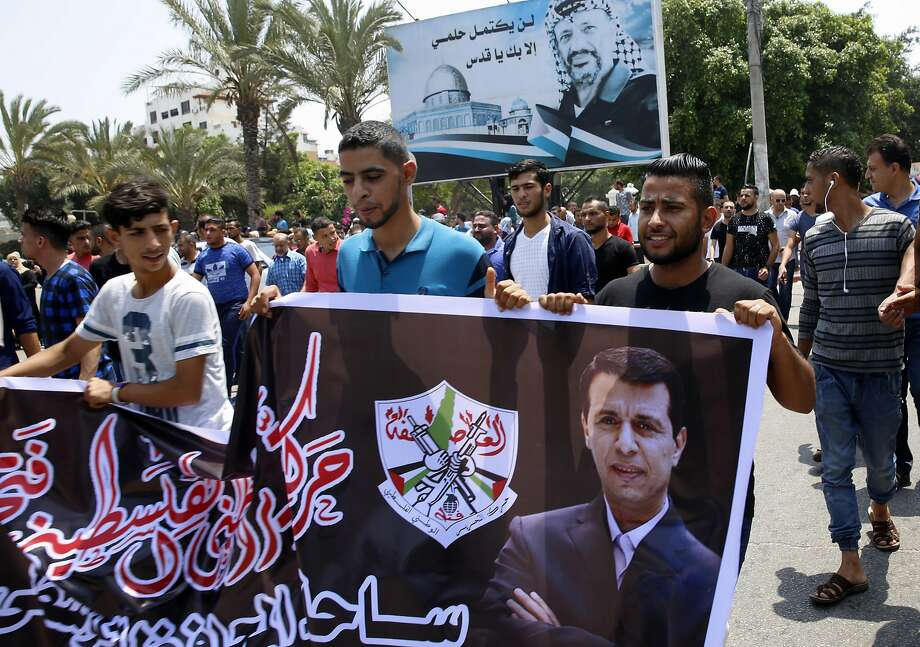 Supporters of exiled former Gaza strongman Mohammed Dahlan carry his picture in Gaza City. Photo: Adel Hana, Associated Press