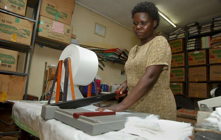 A Ugandan worker cuts sanitary pads made from wastepaper that sell for less than imported pads. Photo: Stephen Wandera, Associated Press