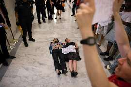 Protesters on Capitol Hill in Washington, July 19, 2017. In a meeting with Senate Republicans on Wednesday, President Donald Trump vigorously defended the all-but-dead Senate health care bill, pressuring lawmakers with both humor and thinly veiled threats. (Tom Brenner/The New York Times)