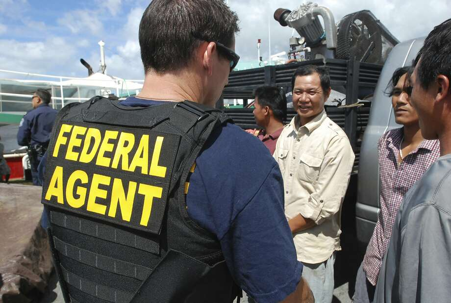 A federal officer talked to foreign fishermen last year during a vessel inspection in Honolulu. Photo: Caleb Jones, Associated Press