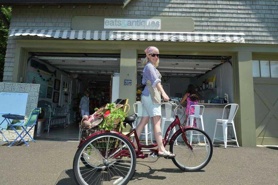 Gina Legnani takes a spin on her bicycle in front of her shop Eats and antiques in Rowayton center on Wednesday July 19, 2017 in Norwalk Conn. Photo: Alex Von Kleydorff / Hearst Connecticut Media / Norwalk Hour