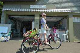 Gina Legnani takes a spin on her bicycle in front of her shop Eats and antiques in Rowayton center on Wednesday July 19, 2017 in Norwalk Conn.