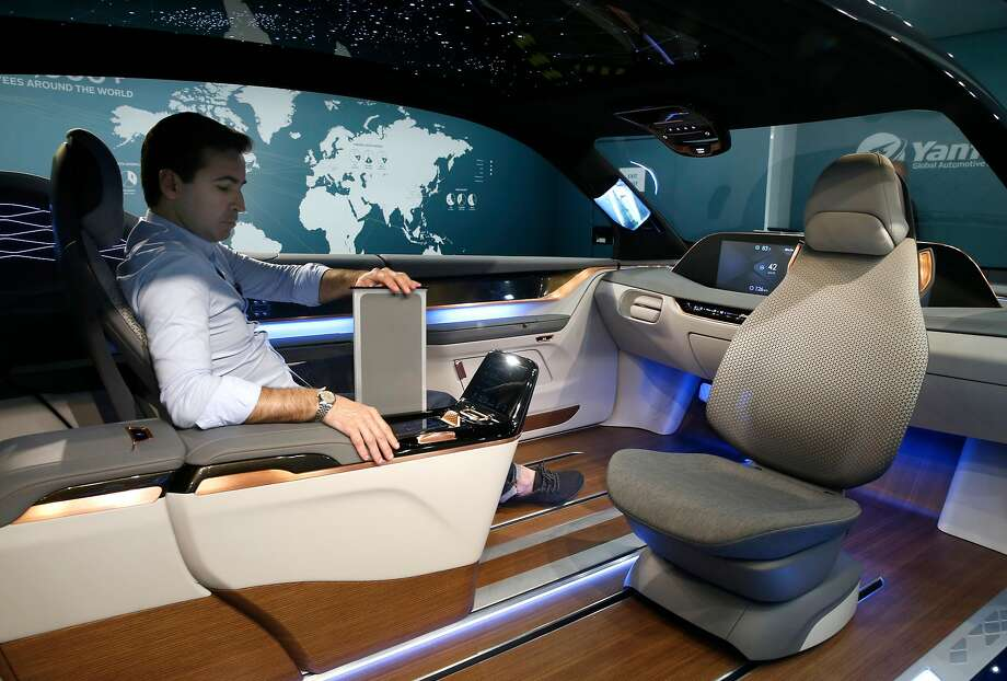 In the self-driving car of the future, all occupants can enjoy other pastimes. In the Experience in Motion (XiM17) variable automobile interior, the vehicle's occupants may choose family, meeting, lounge or drive mode. Here, Leo Schurhaus, principal designer for Yanfeng, pulls up a retractable work table in the meeting configuration. Photo: Paul Chinn, The Chronicle