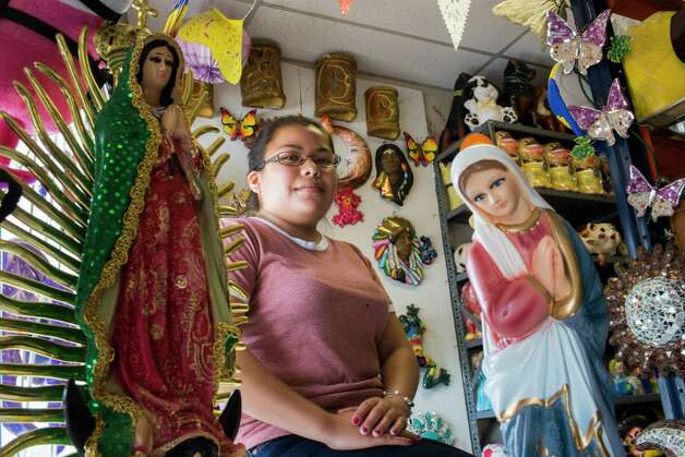 Laura Ramos, 23, looks out the front door of her parents artisan gift shop Artesanias Mexicanas, waiting for customers to come in Wednesday, May 17, 2017 in Houston. The owners have seen the sales drop at the gift shop by at least 20 percent compared to the same period last year. Photo: Marie D. De Jesus, Houston Chronicle / © 2017 Houston Chronicle