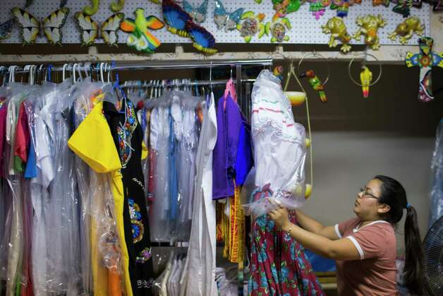 Laura Ramos, 23, undresses a manequin at Artesanias Mexicanas, where she works, Wednesday, May 17, 2017, in Houston. Her parents, who are the owners of the gift shop, have seen the sales drop at the gift shop by at least 20 percent compared to the same period last year. Photo: Marie D. De Jesus, Houston Chronicle / © 2017 Houston Chronicle