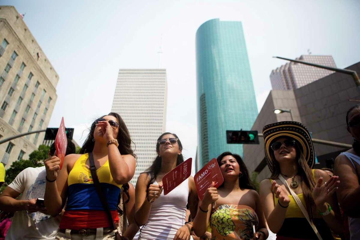 (right to left) Natalia Giraldo, 18, Brigitte Velez, 18, Melanie Gallego, 18, dance to the music of Nacho Acero with some of Houston buildings on the back, Sunday, July 20, 2014, at the Colombian Fest 2014, in Houston. ( Marie D. De Jesus / Houston Chronicle )