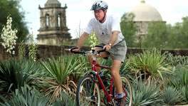 Murphy Emmons, a member of Los Compadres and one-time board chairman, rides his bike near Mission San Jose in 2002.