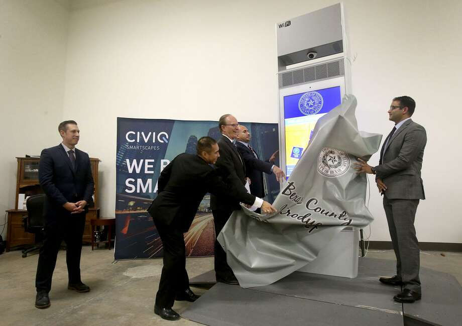 "Bexar County Judge Nelson Wolff (third from left), Thomas Guevara (second from left), Phillip Rico (right of Wolff) and Mohammad Benhalim (far right) unveil Thursday July 20, 2017 a new Bexar County CIVIQ Waypoint Kiosk at the Bexar County Purchasing Department Warehouse. A Bexar County pilot project, the six kiosks will present technology that expands the reach of digital communication, internet accessibility and interpersonal interaction through a spectrum of services for county residents and visitors. The kiosks will be located in the downtown area and will feaure 55""  LCD Wi-Fi Smartscape touch screens that can display content and access to county information, places of interest and photo sharing. The CIVIQ Waypoint kiosks will also have USB charging ports that allow people to charge their electronic devices at no cost. Standing on the far left is Josh Berglund, Director of Technical Services with CIVIQ. Photo: John Davenport, STAFF / San Antonio Express-News / ©John Davenport/San Antonio Express-News"
