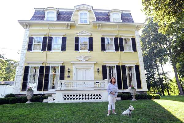 Faith Toraby with her dog Luke in front of the 1873 Federal-style Victorian home she owns with her husband Darius Toraby at 31 Strickland Road in the Cos Cob section of Greenwich, Conn., Wednesday, July 19, 2017.
