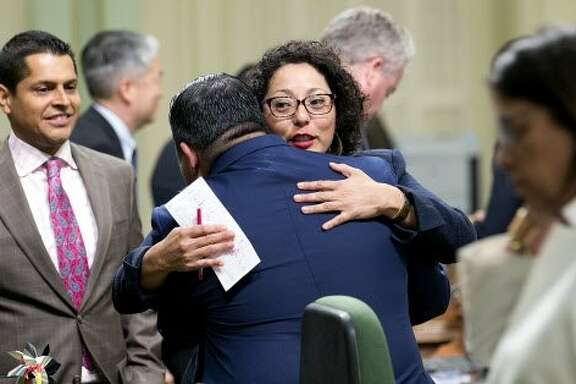 Democratic Assembly members Eduardo Garcia, of Coachella, second from left, and Cristina Garcia, of Bell Garden, second from right, hug after their climate change bills were approved by the Legislature, Monday, July 17, 2017, in Sacramento, Calif. (AP Photo/Rich Pedroncelli)