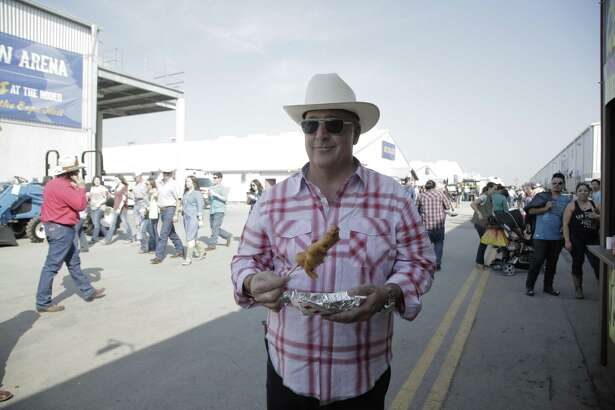 """Bizarre Foods"" host Andrew Zimmern enjoys succulent gator bites at the San Antonio Stock Show and Rodeo."