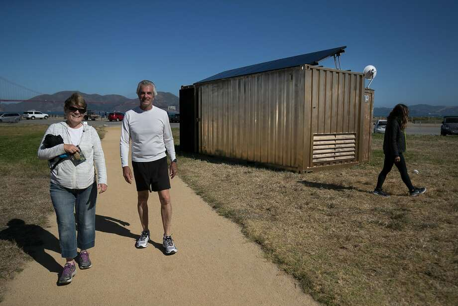 Tracy and Al Brandi walk past a converted container that serves as a portal for Shared Studios in Crissy Field, connecting to other portals around the world in real time. Shared Studios co-founder Michelle Moghtader is in background (right). Photo: Paul Kuroda, Special To The Chronicle