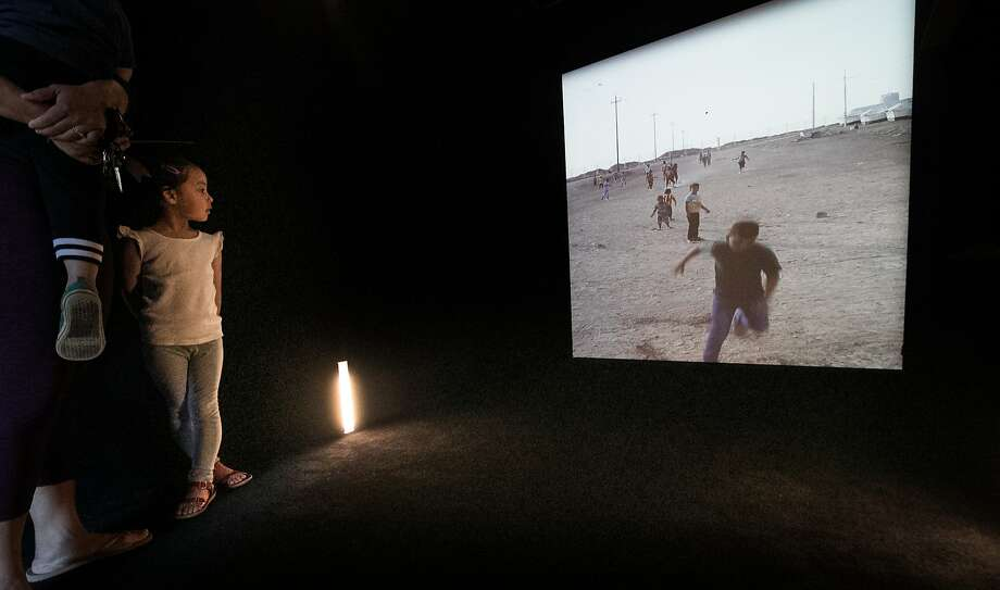 Margot Chinn, 4, watches a video clip in real time from Debaga refugee camp in Erbil, Iraq, through the portal at Crissy Field. Photo: Paul Kuroda, Special To The Chronicle