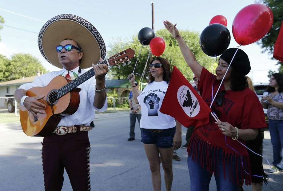 José Treviño (left) of United Farm Workers union plays a song as Rose Lopez (right) joins in singing to honor Jaime Martinez as longtime friends, compatriots and human rights activists gather Thursday for Martinez's funeral procession that passed through the West Side neighborhood where he grew up. Martinez passed away on Sunday after a prolonged battle with lung cancer. Photo: Kin Man Hui /San Antonio Express-News / ©2017 San Antonio Express-News