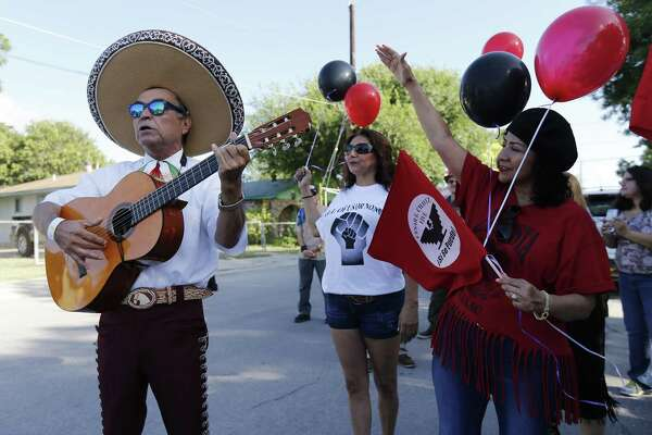 José Treviño (left) of United Farm Workers union plays a song as Rose Lopez (right) joins in singing to honor Jaime Martinez as longtime friends, compatriots and human rights activists gather Thursday for Martinez's funeral procession that passed through the West Side neighborhood where he grew up. Martinez passed away on Sunday after a prolonged battle with lung cancer.