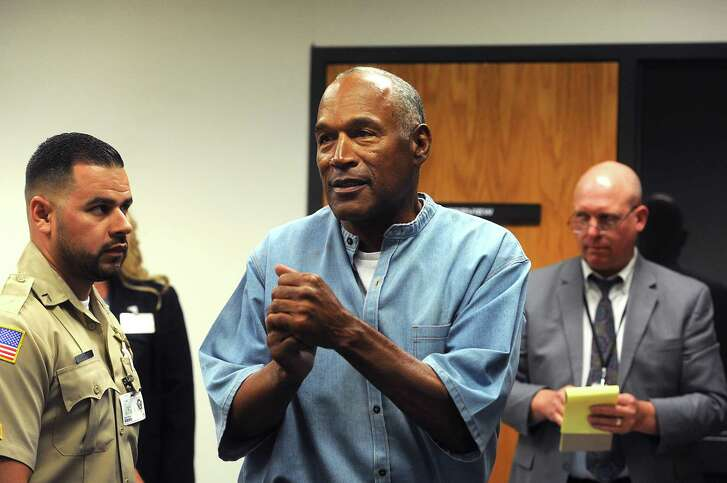 O.J. Simpson, center, was granted parole based on his age and the fact that he has been a model prisoner after serving a nine to 33 year prison term for a 2007 armed robbery and kidnapping conviction.