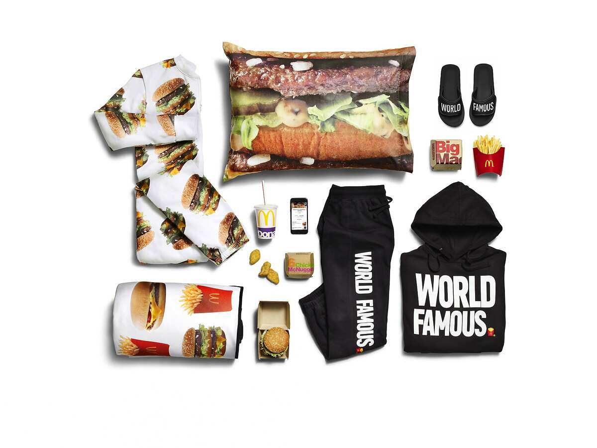 """This photo provided by McDonald's shows the company's McDelivery Collection, a new clothing line that includes an adult-size Big Mac onesie. McDonald's describes the McDelivery Collection as """"a selection of fun, fashion forward items you can wear or use whenever and wherever you order."""" It also includes french fry-themed sweatsuits and sandals, hamburger pillowcases and a picnic blanket dotted with McDonald's items. (Courtesy of McDonald's via AP)"""